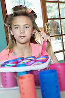 Little girl putting rollers in hair