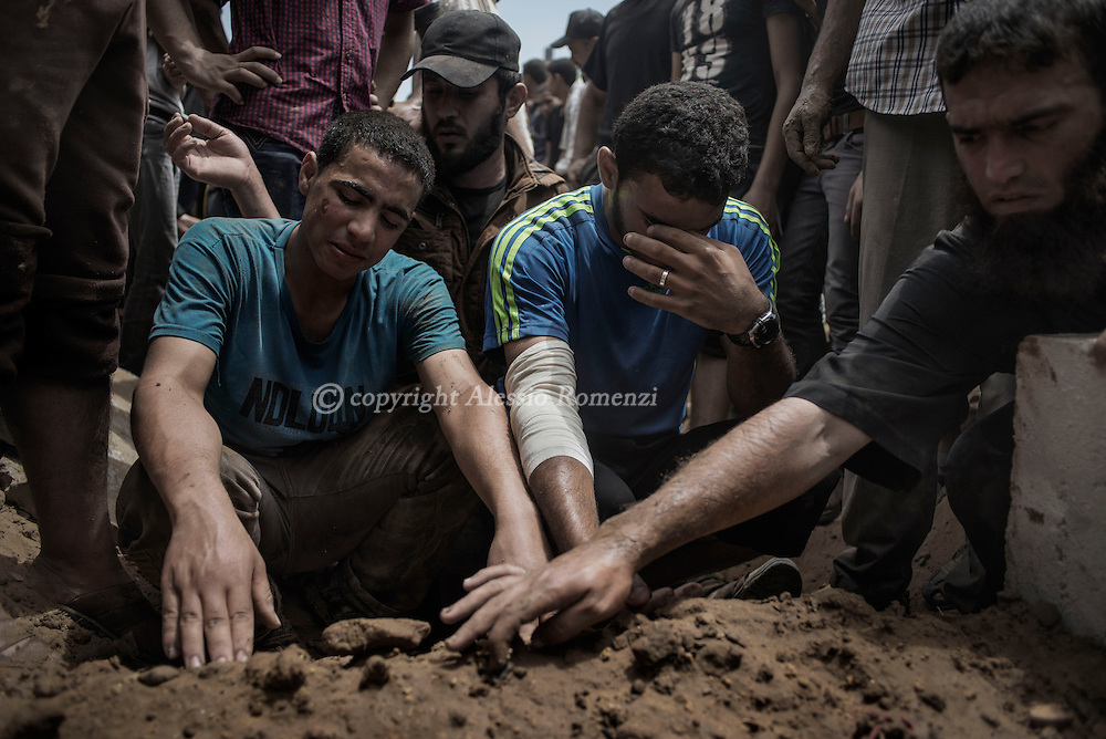 Gaza Strip, Gaza City: Palestinians mourn above a grave during the funeral of 18 members of al-Batsh family who were killed the previous night in Israeli strikes that hit their house as they were targeting Hamas police chief Tayseer al-Batsh on July 13, 2014 in Gaza City.. ALESSIO ROMENZI