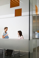 Two women talking in office seen through glass