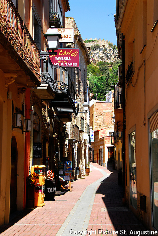 Narrow lanes and colorful buildings make up this street scene in the small Spanish city of Begur, Spain.