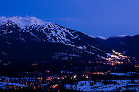The Resort of Whistler, BC glows with lights during the 2010 Olympic Winter Games as Blackcomb and Whistler mountains rise above the pedestrian-only village.