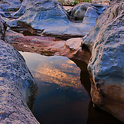 A pool of water reflects the sunset sky at Pedernales Falls State Park, Texas.