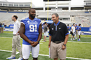 Kentucky defensive end Farrington Huguenin, left, talks with athletics director Mitch Barnhart during the University of Kentucky's annual media day, Friday, Aug. 07, 2015 at Commonwealth Stadium in Lexington.