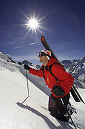 Male skier hiking up steep mountain slope