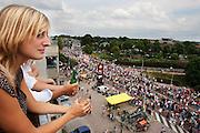 Een vrouw kijkt vanaf het balkon naar de wandelaars die de laatste meters van de Nijmeegse Vierdaagse afleggen op de Via Gladiola, zoals de Sint Annastraat heet tijdens het wandelevenement.