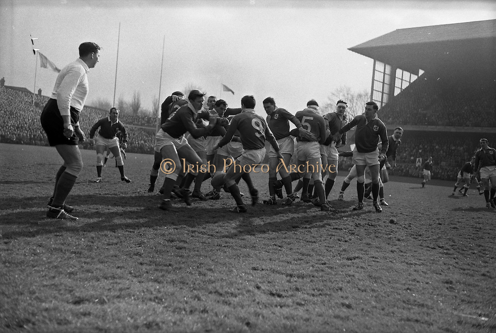 Ireland's number 9, Kelly, getting the ball away, ..Irish Rugby Football Union, Ireland v Wales, Five Nations, Landsdowne Road, Dublin, Ireland, Saturday 7th March, 1964,.7.3.1964, 7.3.1964,..Referee- A C Luff, Rugby Football Union, ..Score- Ireland 6 - 15 Wales, ..Irish Team, ..F S Keogh, Wearing  Number 15 Irish jersey, Full Back, Bective Rangers Rugby Football Club, Dublin, Ireland,  ..P J Casey, Wearing number 14 Irish jersey, Right Wing, University College Dublin Rugby Football Club, Dublin, Ireland, .. M K Flynn, Wearing number 13 Irish jersey, Right Centre, Wanderers Rugby Football Club, Dublin, Ireland, ..J C Walsh,  Wearing number 12 Irish jersey, Left Centre, University college Cork Rugby Football Club, Cork, Ireland,..K J Houston, Wearing number 11 Irish jersey, Left Wing, Queens University Rugby Football Club, Belfast, Northern Ireland,..C M H Gibson, Wearing number 10 Irish jersey, Stand Off, Cambridge University Rugby Football Club, Cambridge, England, and, N.I.F.C, Rugby Football Club, Belfast, Northern Ireland, ..J C Kelly, Wearing number 9 Irish jersey, Scrum Half, University College Dublin Rugby Football Club, Dublin, Ireland,..P J Dwyer, Wearing number 1 Irish jersey, Forward, University College Dublin Rugby Football Club, Dublin, Ireland, ..P Lane, Wearing number 2 Irish jersey, Forward, Old Crescent Rugby Football Club, Limerick, Ireland, ..T A Moroney, Wearing number 3 Irish jersey, Forward, University College Dublin Rugby Football Club, Dublin, Ireland, ..W A Mulcahy, Wearing number 4 Irish jersey, Captain of the Irish team, Forward, Bective Rangers Rugby Football Club, Dublin, Ireland,  ..M W Leahy,  Wearing number 5 Irish jersey, Forward, University college Cork Rugby Football Club, Cork, Ireland,..E P McGuire,  Wearing number 6 Irish jersey, Forward, University college Galway Rugby Football Club, Galway, Ireland,..M G Culliton, Wearing number 8 Irish jersey, Forward, Wanderers Rugby Football Club, Dublin, Ireland, ..N A Murphy, Wearing numb