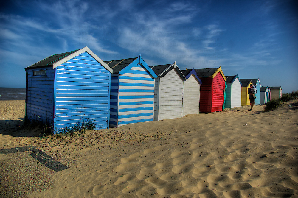 Beach huts at Southwold, Suffolk, England with father and young son walking by on golden sand