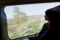 Florence, Italy - 28 April, 2012: A first class passenger looks at the Tuscany landscape on the Milan bound ITALO, Europe's first private operator of high-speed, domestic trains in Italy, in Florence, Italy, on April 28, 2012. The company's president is Ferrari chairman Luca Cordero di Montezemolo, one of the shareholders along with other private entrepreneurs like luxury businessmen Diego Della Valle, the French railway company, Italy's largest retail bank and the country's largest insurer. Italy's NTV (Nuovo Trasporto Viaggiatori) is the first company in Europe to compete with the state-run Trenitalia on high-speed service. When at full regime at the end of the year, 25 innovative trains will connect nine Italian cities, from Salerno to Milan, from Turin to Venice at 300km per hour. Italo passengers will board on stable trains that do not rely on a locomotive car, but has engines underneath each of the 11 carriages to increase capacity as well as safety.<br /> <br /> Ph. Gianni Cipriano for The New York Times