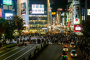 Night photography of a crowed of pedestrians crossing a four way zebra crossing at Shibuya crossing in central Tokyo, Japan