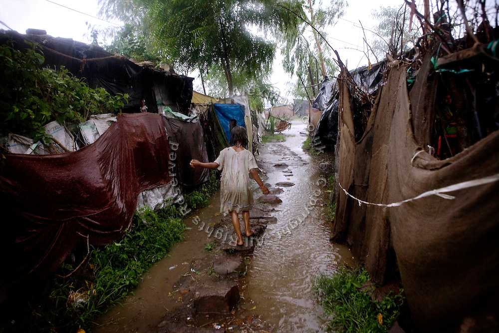 Poonam, 6, is walking under the late monsoon rain on a path in the impoverished Oriya Basti Colony, Bhopal, Madhya Pradesh, near the abandoned Union Carbide (now DOW Chemical) industrial complex.