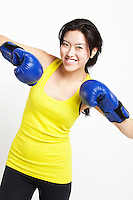 Portrait of happy Asian female boxer wearing blue gloves against white background