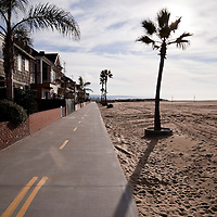 The Newport Balboa Bike Trail starts just past Newport Pier and extends toward the end of Balboa Peninsula. The Newport Balboa Bike Trail is lined with oceanfront homes and Balboa Beach along the Pacific Ocean. Photo is vertical and high resolution.