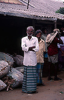 Sri Lankan men gathered at a market stall.