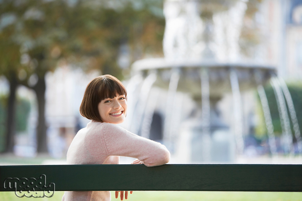Young woman sitting on bench in front of fountain looking over shoulder
