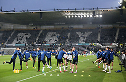 Derby County players warm up on the pitch before the match begins