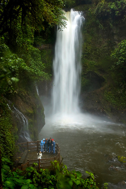 Tourists Stop And Pose For Photographs In Front Of The Magia Blanca Waterfall At The La Paz Waterfall Gardens In Costa Rica
