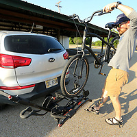 Matthew Knight of Tupelo, unloads his bike after arriving at the Farmers Depot Wednesday night for the Downtown Tupelo Bike Gang's first ride through downton.