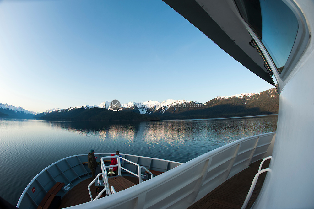 Passengers on the bow of a small cruise ship in Alaska.