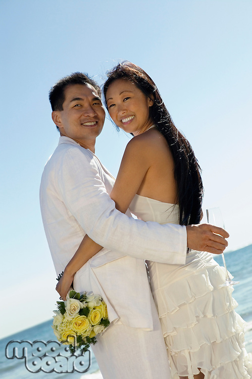 Bride and Groom Embaracing on Beach