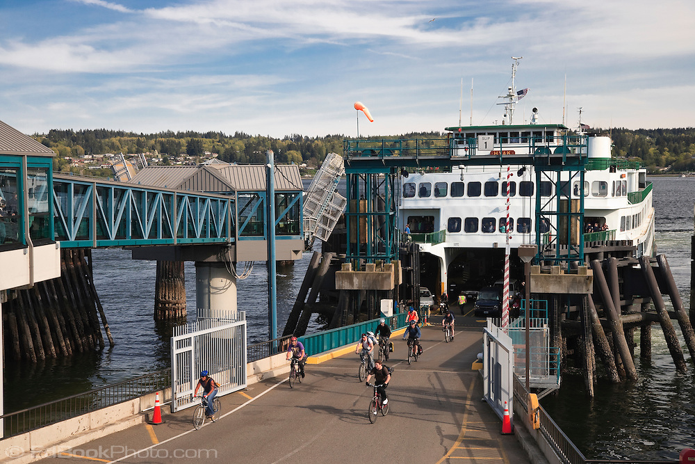 Commuters on bicycles disembark first from the Washington State ferry Hyak at Bremerton on the Kitsap Peninsula in Puget Sound, Washington, USA