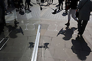 Seen through a polished sheet glass window, a pigeon takes off among pedestrians, appearing as a symmetrical image.