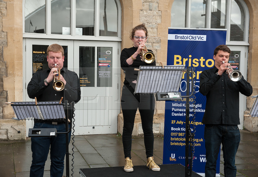 """© Licensed to London News Pictures. 27/07/2015. Bristol, UK.  """"Fanfare for Bristol"""", titled """"At the Top of the Tide"""", composed by David Mitcham, commissioned by Bristol Proms 2015.  Picture shows trumpeters l-r: Chris Hart, Helen Whitemore, Gideon Brooks, performing live for the Mayor of Bristol, George Ferguson and Artistic Director of the Bristol Old Vic, Tom Morris for the first time at Bristol's famous Temple Mead train station, heralding the opening of the Bristol Proms 2015.  David Mitcham's  """"At the Top of the Tide"""" was inspired by 'Bristol's inextricable links to the sea'.  The first performance by Arc Brass took place outside the Engine Shed, and throughout the day, performances took place at the Watershed, Pero's Bridge, the Wills Memorial Bell Tower and finally at Bristol Old Vic itself. David Mitcham, who has worked extensively for the BBC Natural History Unit based in Bristol said: """"I am thrilled that my Fanfare """"At the Top of the Tide"""" has been chosen for the city of Bristol and to open Bristol Proms 2015. I hope the Fanfare represents the rich diversity of Bristol, its maritime and industrial heritage as well as being a celebration of the spirit of the city and the energy it will carry into the future.""""  Bristol Proms 2015 runs from today, 27th July to 1st August and features some of the world's finest musicians including Alison Balsom, Miloš Karadaglić, Pumeza Matshikiza and Daniel Hope.  Photo credit : Simon Chapman/LNP"""