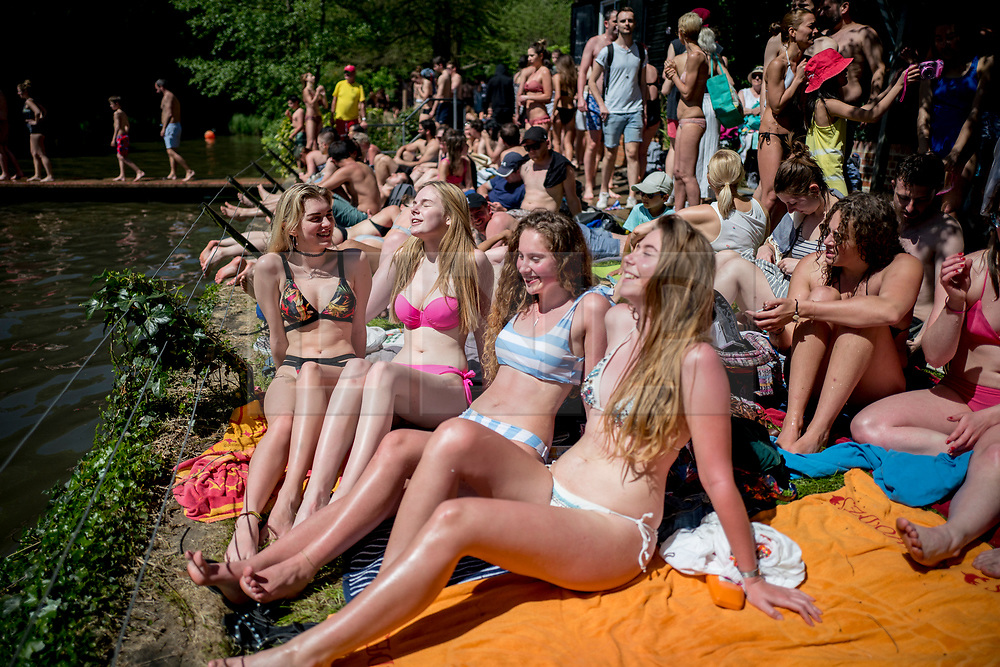 © Licensed to London News Pictures. 07/05/2018. London, UK. Lara Mckenzie, Jenna Vivers, Ralitsa Balkanska and Iliriana Lleshi sunbathe near Hampstead Heath Mixed Bathing Pond in north London as temperatures hit 28C on the hottest May bank holiday since 1999 on Monday, May 7, 2018. Photo credit: Tolga Akmen/LNP
