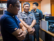 "26 JUNE 2015 - BANGKOK, THAILAND:  Thai Police Colonel KITTIGORN BOONSOM, center, tells representatives of the Foreign Correspondents' Club of Thailand (FCCT) that a scheduled announcement by Human Rights Watch (HRW) about human rights in Vietnam was cancelled by order of the Thai government. HRW was scheduled to launch a new report, ""Persecuting 'Evil Way' Religion: Abuses against Montagnards in Vietnam"", at the FCCT in Bangkok Friday morning. The report made no mention of the human rights situation in Thailand. The Thai Ministry of Foreign Affairs (MFA) contacted HRW Thursday afternoon and asked them to cancel the program because it was a ""sensitive"" matter that could impact on Thai-Vietnam relations. HRW told the MFA that they would go ahead with the report's release. Friday morning, before the report was scheduled to be released, Thai police officers arrived at the FCCT and cancelled the event. Phil Robertson, deputy director of Human Rights Watch's Asia division, said, ""By stepping in to defend a neighboring state's human rights violations against a group of its people and interrupting a scheduled press conference, Thailand's military junta is violating freedom of assembly and demonstrating its contempt for freedom of the press.""      PHOTO BY JACK KURTZ"