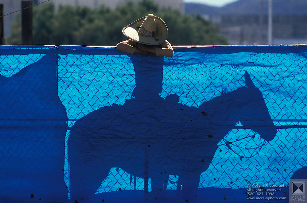 """""""Even Cowboys Get the Blues"""" Mexican cowboy at Mexican rodeo, horseback rests on corral gate covered with blue sheet, Tucson, Arizona.vaquero azul.©1986 Edward McCain/McCain Creative, Inc. All Rights Reserved 520-623-1998"""