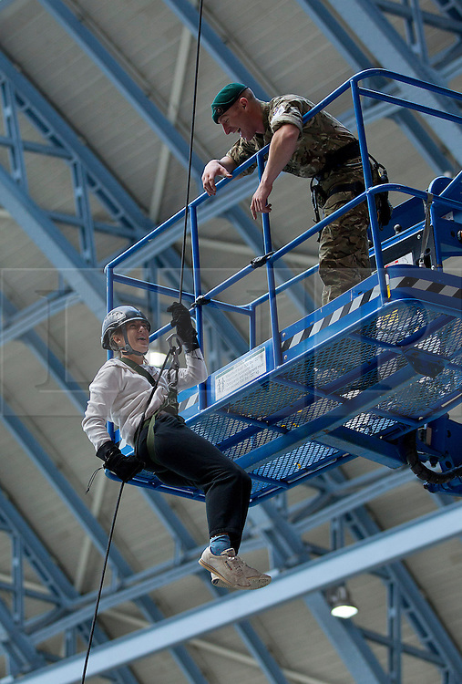 © Licensed to London News Pictures. 14/09/2012. LONDON, UK. Under the instruction of a Royal Marine Commando, a volunteer abseils from the roof of St Pancras International in London today (14/09/12). The abseil saw 15 abseilers descend from the roof of the station in an attempt to raise more than £150,000 for the Commando Spirit Appeal on behalf of the Royal Marines Charitable Trust. Photo credit: Matt Cetti-Roberts/LNP