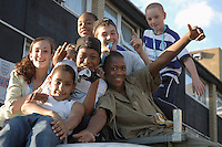 Lively group of children climbing and jumping on van parked on their housing estate in Kensal Green West london.