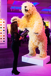 "London, March 4th 2015. Sotheby's in London hosts ""one of the most extraordinary collections of our time"", an anonymous collector's vast assembly of fine art pieces, including skulls, bear sculptures, paintings and installations. PICTURED: A woman examines Paola Pivi's ""Life Is Great"", a giant polar bear sculpture covered in feathers."