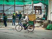 01 APRIL 2014 - BANGKOK, THAILAND:  A man rides his bike past the entrance to a construction site in the Bangkok flower market. The Yodpiman Flower Market (also called Pak Khlong Talat) is being renovated and gentrified. The market opened in 1961 and has been a Bangkok landmark for more than 50 years, is being turned into a high end mall. Many of the flower and vegetable vendors in the market may be forced out.   PHOTO BY JACK KURTZ