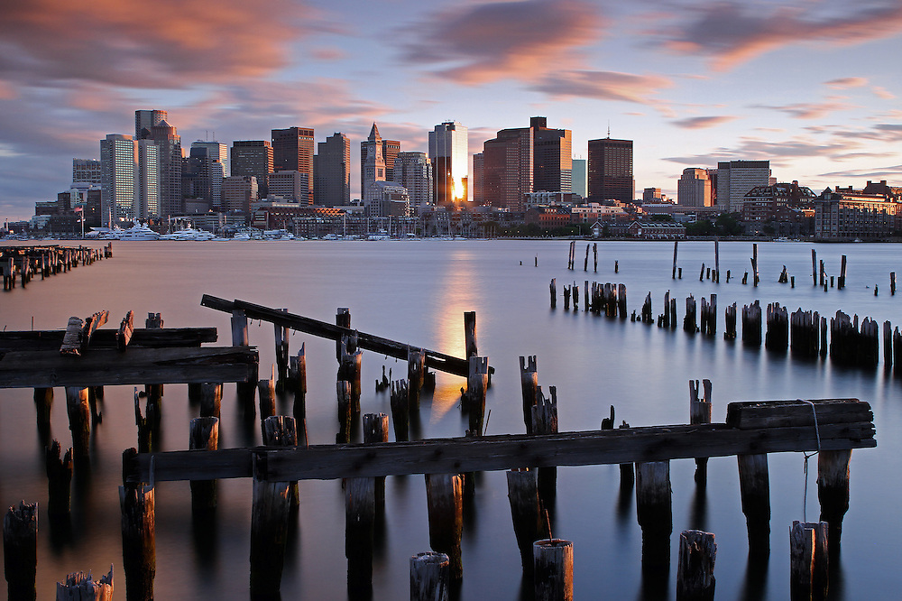 One of a kind Boston skyline photography by New England based award winning photographer Juergen Roth showing landmarks such as Boston Downtown, Custom House of Boston, New England Aquarium, John Hancock Tower, Boston harbor hotel, Financial District, US Coast Guard, National Oceanic and Atmospheric Administration, Rowes Wharf, International Place and sailboats docked at the Boston Harbor. The Boston cityscape photography image was captured on a late afternoon shortly before sunset.<br />