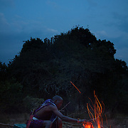 Dixon cooks a side of a goat over the open fire. It is mainly Maasais who live in the Loita Hills up above the Serengeti plains. They live in small villages and communities called bomas and live mainly of raising and selling live stock such as cattle and goats. Its a very remote region in Kenya, hard to get to without a four wheel drive with very little infrastructure and up till 2010 no mobile phone network. The Maasais are well known though out Kenya and the world for their colorful clothing and their way of keeping their old traditions alive.Meat is an important part of the Maasai's diet, as well as maze and milk. Dixon is a member of the S.A.F.E theatre group. S.A.F.E is a charity which educates children and young people about life skills and how to protect themselves from HIV and other STIs through performance. They also do performances about Female Genital Mutilation, an old tradition amongst the Maasais in Loita and a very brutal and controversial custom which S.A.F.E is trying to eradicate.