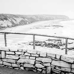 Laguna Beach Crystal Cove State Park panorama scenic overlook railing with the beach and Pacific Ocean in black and white