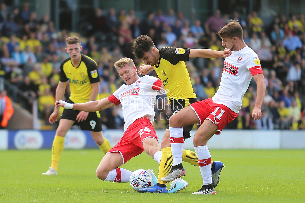 Burton Albion midfielder Scott Fraser (8) is halted by Rotherham United forward Michael Smith (24) and Rotherham United midfielder Dan Barlaser (11) during the EFL Sky Bet League 1 match between Burton Albion and Rotherham United at the Pirelli Stadium, Burton upon Trent, England on 17 August 2019.