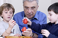(from left) Ryan Bonanno,4; John Valassiades and Grant Kopan, 4 with the red eggs of a traditional Greek Orthodox Easter, Monday, March 24, 2008.  The bowl that held the eggs is hand carved and hand painted.