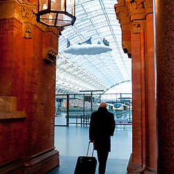 London, UK - 18 April 2013: A passenger walks by with her luggage in St Pancras International station on the day a new piece of public art, Cloud: Meteoros by Lucy Orta, is unveiled above the Grand Terrace.