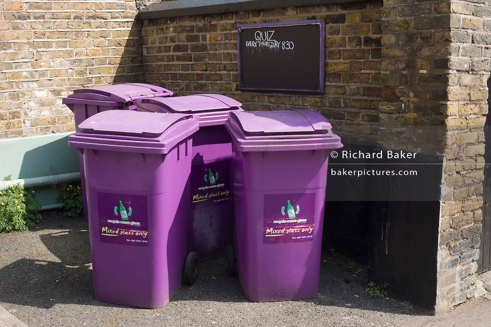 Purple bins gathered in a corner of a pub's property with a sign for a  Pub Quiz every Thursday at 8.30.