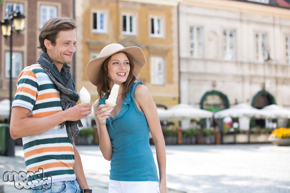 Tourist couple enjoying ice cream cones during vacation