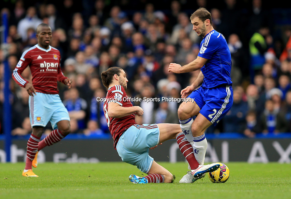 26 December 2014 - Barclays Premier League - Chelsea v West Ham - Andy Carroll of West Ham with a strong tackle on Branislav Ivanovic of Chelsea -  Photo: Marc Atkins / Offside.