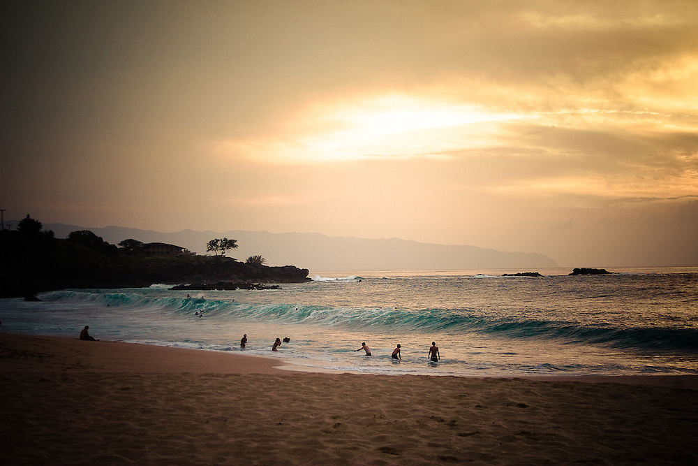 The sun sets at Waimea Bay amongst people frolicking in the surf at the north shore, Oahu, Hawaii, USA.