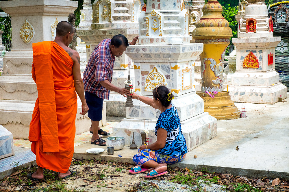 A Thai family returns the ashes of a relative to a burial Chedi after a ceremony to honor the dead during Songkran 2017 festivities in Nakhon Nayok, Thailand. PHOTO BY LEE CRAKER