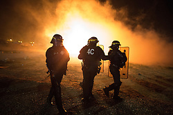 """© Licensed to London News Pictures . 23/10/2016 . Calais , France . Riot police charge residents at the Calais migrant camp known as """" The Jungle """" , in Northern France , on the evening before the start of the eviction and destruction of the camp . Photo credit: Joel Goodman/LNP"""