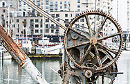 up close photography of an old rusty Boat Crane, by the harbour in Aarhus Denmark, with the newly build modern housing in the background