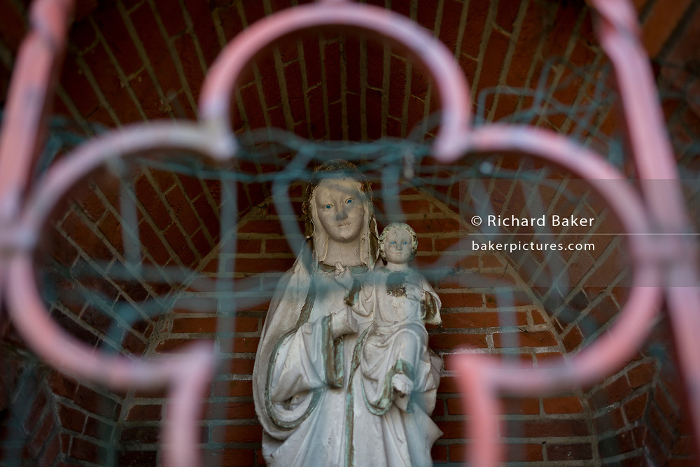 A catholic shrine showing Mary and baby Jesus, behind wire and iron gates in woods, on 25th March, in Everberg, Brabant, Belgium.