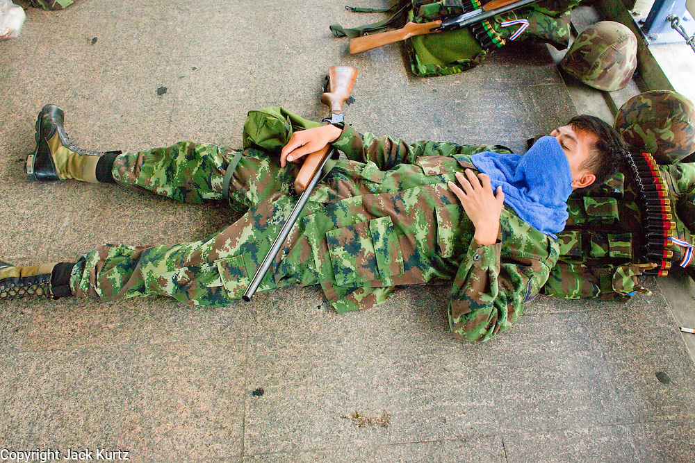 Apr. 19 2010 - BANGKOK, THAILAND: A Thai soldier armed with a shotgun sleeps in the elevated walkway above the Silom financial district in Bangkok Monday. Hundreds of Thai soldiers, including reservists and front line units, and riot police moved into the Silom financial district Monday, not far from the red-shirts' main protest rally site, in Ratchaprasong. The heavy show of force is to prevent the Red Shirts from entering the Silom area. Many of soldiers were greeted as heros by workers in the area, who oppose the Red Shirts.   Photo by Jack Kurtz