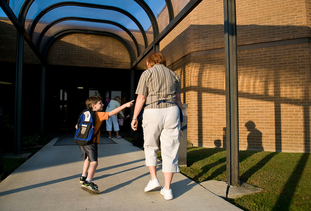 Lissa Riley walks with Jared West, 5, into the school building after getting off the bus. .