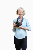 Portrait of smiling senior female photographer with camera against white background